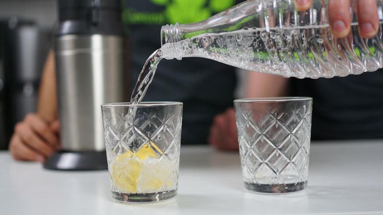 Wasser wird aus Glaskaraffe des Crystal 2.0 in ein Glas geschüttet