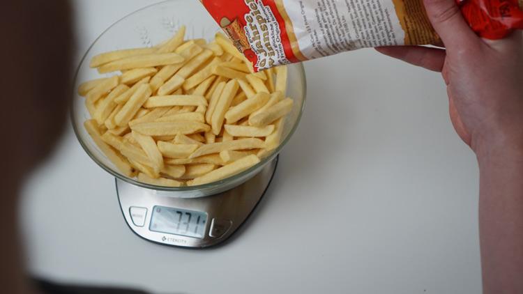 Tk-Pommes werden in Schale auf Küchenwaage geschüttet