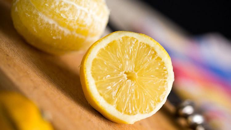 Aufgeschnittene Zitrone neben geschälter Zitrone